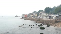 Littoral slum landscape in rainy day, stony shore and hovels on hillside. Stock Footage