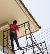 worker stand on girder painting pillar - stock photo