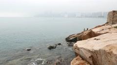 Rocky cliff at Yue Mun Point, haze horizon, fishermans on rocks Stock Footage