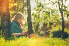 Pretty young caucasian woman  sitting outside under a tree talking on smartphone Stock Photos