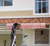 worker using drill to install awning - stock photo