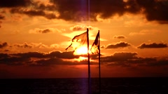 Tattered waving flag in sunset - looped Version - stock footage