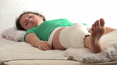 4k Girl with broken leg in a plaster cast in hospital bed Stock Footage
