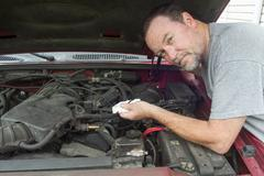 Mechanic Checking Oil Levels On A Older Vehicle Stock Photos