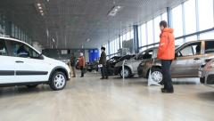 Auto dealer - people shopping for cars at dealership Stock Footage