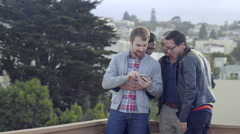 Gay Men Look Through Their Friend's Smart Phone Pics At A Party (4K) Stock Footage