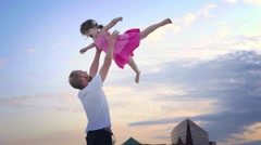Father playing with daughter girl trowing in air at sunset over LA cityscape. Stock Footage