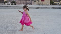 Happy girl in pink dress running barefoot outdoors. Slow motion. Child kid Stock Footage