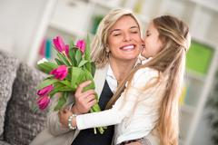 Girl  giving flowers to his mom on mother's day Kuvituskuvat