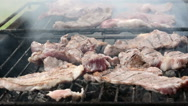 Stock Video Footage of Cook Rotates on Grill Pork Chops and Steaks