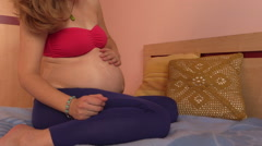 Pregnant woman moisturizing belly with cream lotion Stock Footage