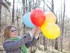Carefree Lifestyle Happy Young Woman with Colorful Balloons outdoor. Beautifu - stock photo