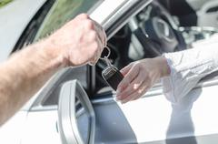 Man giving car key to a woman - stock photo