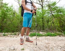 sporty hiker walking through forest - stock photo