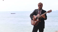 European man  plays guitar against sea islands and boat Stock Footage