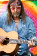 Bearded middle-aged hippie man playing the guitar - stock photo