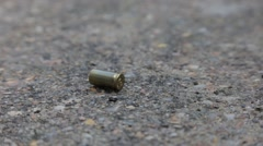 Drawing chalk outlines around bullet shells on gravel Stock Footage