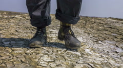 Feet Of Researcher Walking On Split Soil At Valley Stock Footage