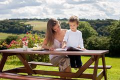 Mother and son, reading a book outdoor, summer day - stock photo