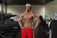 Aesthetic Man Listening Music In Modern Fitness Center - stock photo