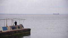 A fisherman on the dock against the sea with the ship Stock Footage
