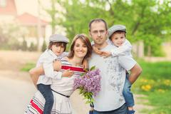 Family of four, mother, father and two boys, parent having the kids on piggy  Stock Photos
