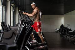 Mature Man Doing Aerobics Elliptical Walker In Gym - stock photo