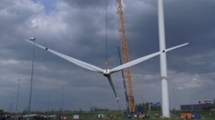 Slowly and precise hoisting the rotor blades of a wind turbine - wide shot Stock Footage