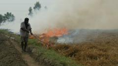 Farmer sets fire to his land in India Stock Footage