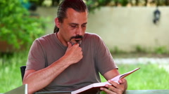 Middle age brunette man reading a book Stock Footage