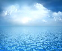 Blue ocean with white clouds on horizon Stock Illustration