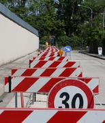 speed limit sign and hurdles in the road excavation - stock photo