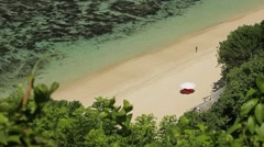 Lonely umbrella and blue sea waves on the beautiful tropical beach on Bali islan Stock Footage