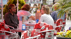 People sitting on the terrace of a bar an sunny morning Stock Footage