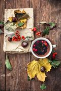 Cup with tea and fallen autumn leaves on wooden table - stock photo