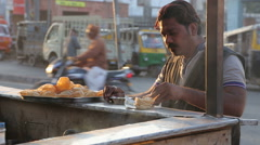 Indian man eating local food prepared at market stand in Jodhpur. - stock footage