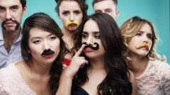 Multi racial group of people wearing false mustache for movember slow motion - stock footage