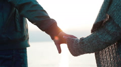 Close up of couple holding hands. Young couple in love coming closer to see sea Stock Footage