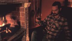 Man drinks red wine in front of fireplace - stock footage