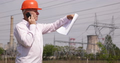 Electrician Engineer Man Talk Mobile Phone Power Plant Energy Station Plan Paper Stock Footage