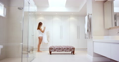 Beautiful young woman deciding what to wear holding up dress in bathroom Stock Footage