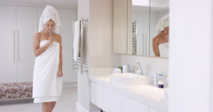 Beautiful woman singing in bathroom wearing white towel dancing in front of Stock Footage