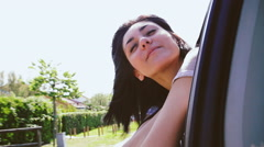 Cute young woman enjoying fresh air from window car Stock Footage