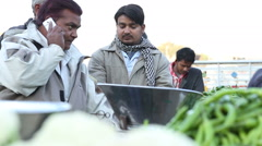 Indian men at the market, one of them counting money, other talking on phone. Stock Footage