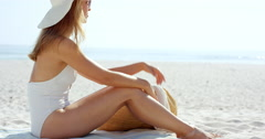 Beautiful young womansitting on beach wearing one piece white bathing suite Stock Footage