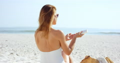 Beautiful young woman applying sunscreen to shoulder the beach wearing one piece Stock Footage