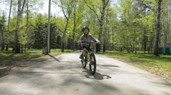 Kid riding bike bicycle in springtime Stock Footage