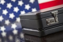 Black Leather Briefcase Resting on Table with American Flag Behind. - stock photo