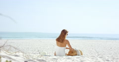 Wide shot woman applying sunscreen to arms  on beach wearing one piece white Stock Footage