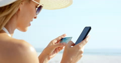 Woman using credit card shopping online with mobile phone at the beach on Stock Footage